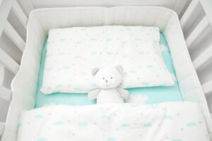 Small, white teddy bear in baby bed. Linen with clouds. Top view.