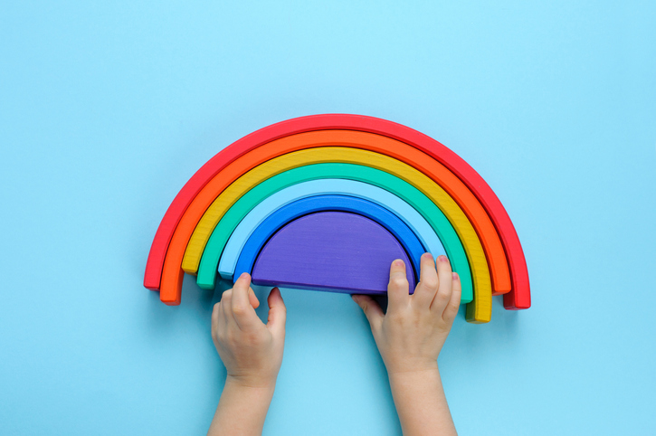 Kids hands playing with wooden toy rainbow on blue background