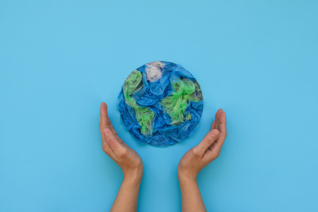 Two hands supporting a papercraft model of the globe