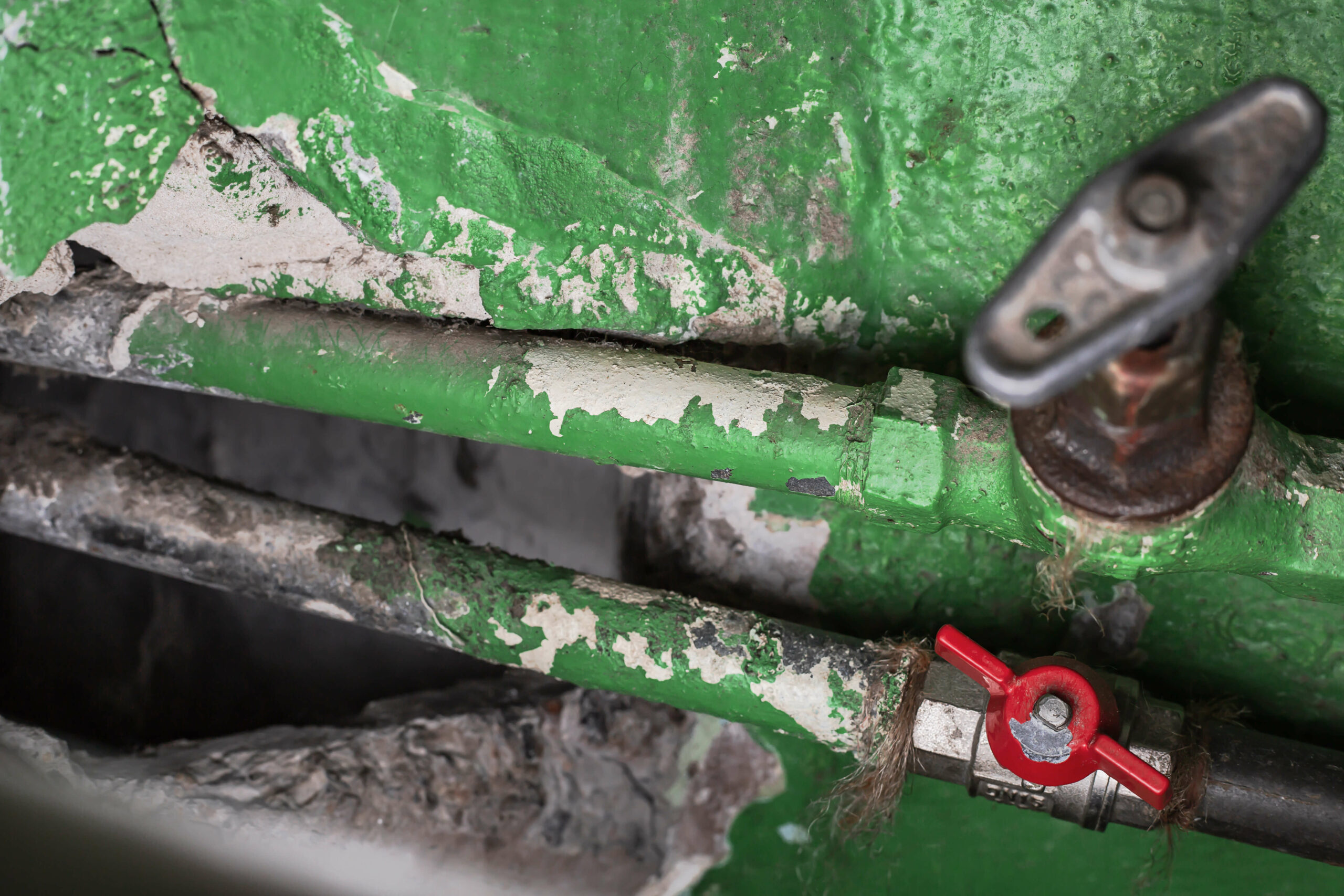 Old plumbing, showing pipes and valves covered in flaking, green paint